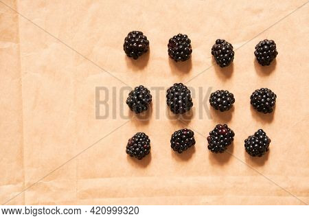 Twelve Blackberries On A Beige Craft Paper Background. Berries Laid Out In The Form Of A Rectangle.