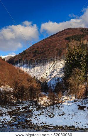 Stream Between Snowy Mountains With Deciduous And Conifer Forest