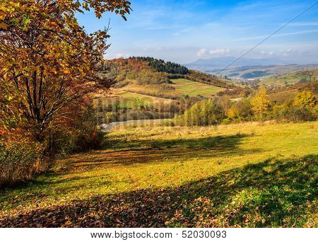 Autumn Landscape With Meadow And Village  In Mountains