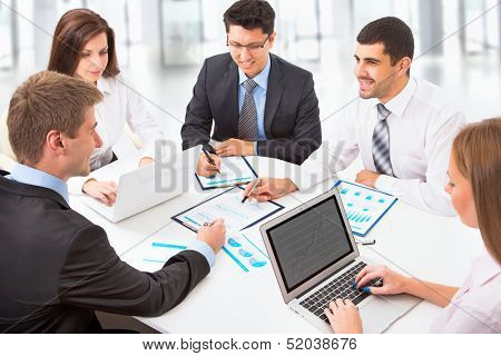 Young business people sitting at desk, using computer at business training, smiling.