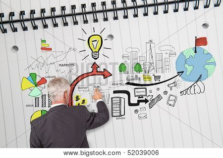 Rear view of businessman drawing economical graphics on huge notepad poster