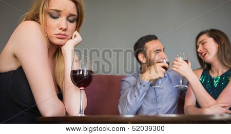 Blonde woman feeling envious of two people are flirting beside her in a nightclub