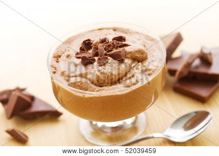 Bowl of mousse au chocolat with chocolate pieces on wood