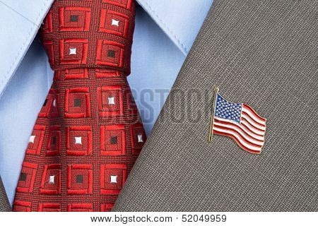An American flag lapel pin on the collar of a business suit jacket shows patriotism