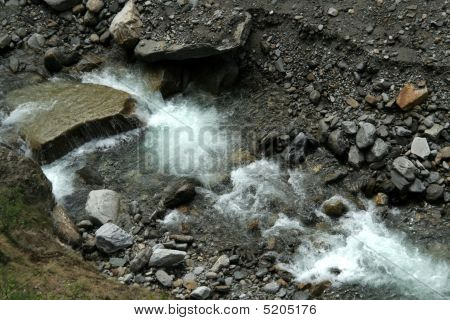 Pattern of spray of water flowing between stones and over pebbles poster