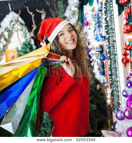 Portrait of happy young woman in Santa hat carrying shopping bags at Christmas store