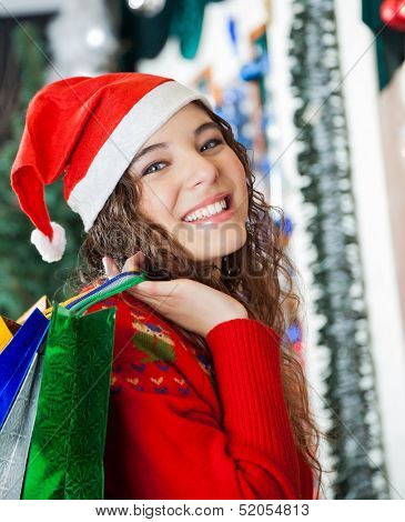 Portrait of beautiful young woman in Santa hat carrying shopping bags at Christmas store