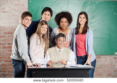 Portrait of confident male professor and students at desk against greenboard in classroom