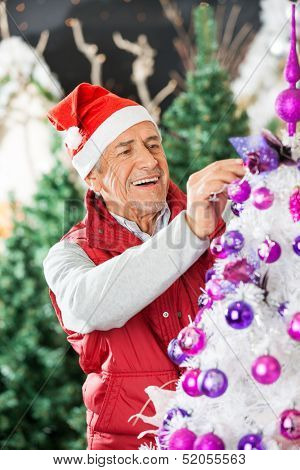 Happy owner in Santa hat decorating Christmas tree at store