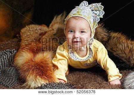 Blue-eyed baby lying on fur litter near the hauberk fox pelt in the background poster