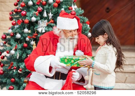 Side view of girl taking gift from Santa Claus against Christmas tree