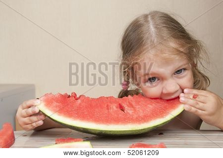 Two-year-old girl eating watermelon with cheerful faces
