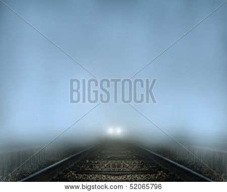 a train coming down tracks at night in the fog