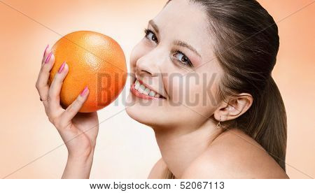 Playful young woman with orange fruit