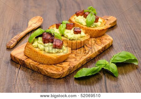 Bruschette with avocado cream and sausage on a wooden olive board poster