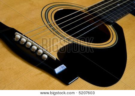 The bridge and strings of and acoustic guitar poster