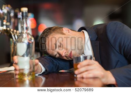 Unconscious businessman holding whiskey glass lying on a counter in a classy bar