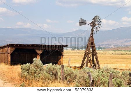 Old wind driven water pumping windmill stands next to an empty storage shed on a cattle ranch in a California mountain valley. poster