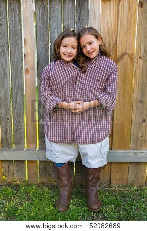 twin girls fancy dressed up pretending be siamese with his father shirt