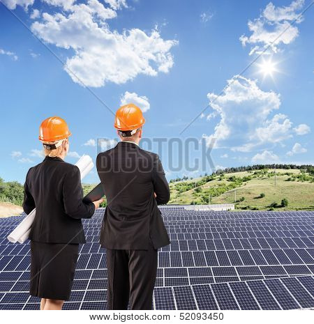 Team of architects examining solar panels under sunny sky, Macedonia, shot with a tilt and shift lens