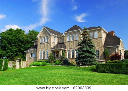 Large upscale residential home with bright green lawn and blue sky
