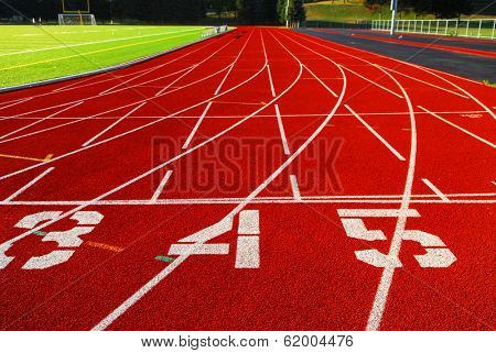 Lanes of a red race track with numbers and green football field