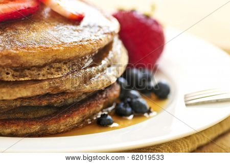 Stack of buckwheat pancakes with fresh berries and maple syrup