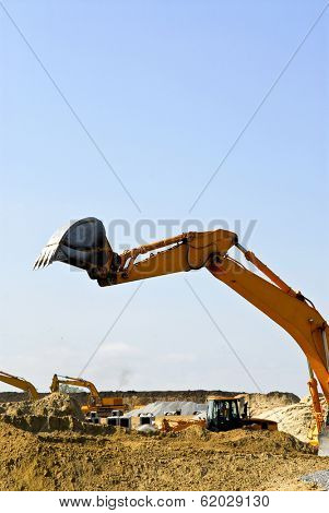 Yellow bulldozer machines digging and moving earth at construction site