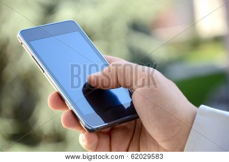 Close up of a businessman hand holding and using a smart phone outdoors