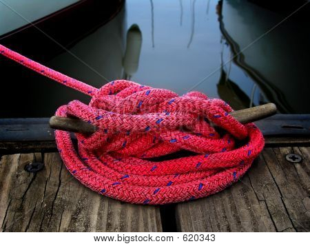 red boaters rope tied to dock securing boat poster