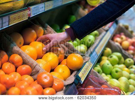 choosing an orange in grocery store