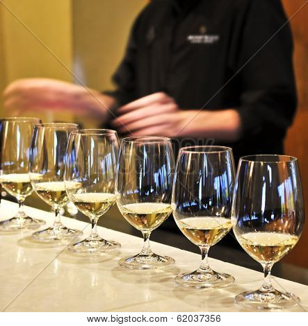 Row of white wine glasses in winery tasting event