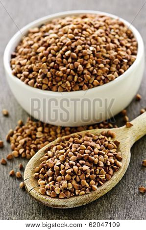 Buckwheat seeds on wooden spoon and in bowl