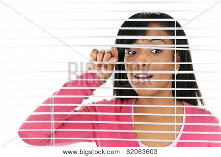 Young black woman looking through horizontal venetian blinds