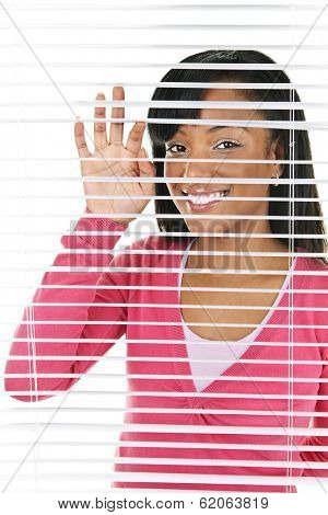 Happy young black woman looking through horizontal venetian blinds