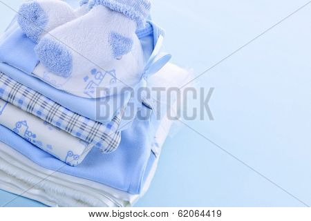 Stack of boy infant clothing for baby shower on blue background