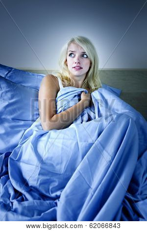 Sleepless blonde woman scared at night in bed