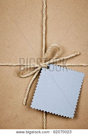 Gift package and blue tag in brown paper wrapper tied with string close up
