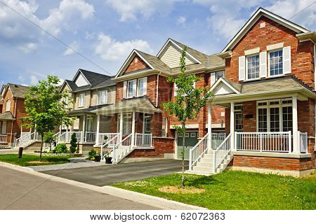 Suburban residential street with row of red brick houses