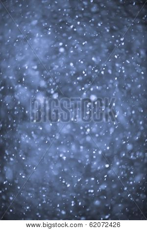 Background of snow flurry falling at night with motion blur