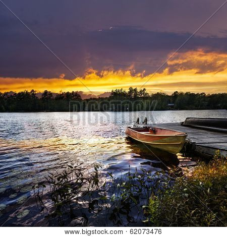Rowboat tied to dock on beautiful lake with dramatic sunset