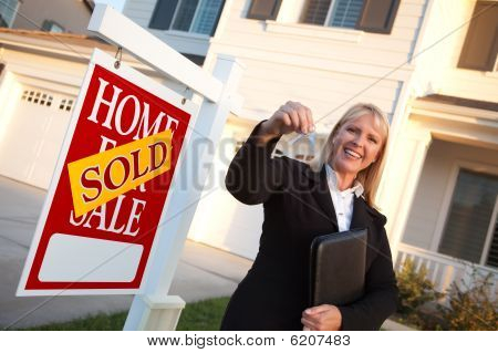 Female Real Estate Agent Handing Over The House Keys