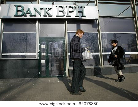KRAKOW, POLAND-MARCH 15: Unidentified people walk past an office of Bank BPH on March 15, 2004 in Krakow, Poland. Bank BPH Banku is a Polish bank that is 66 percent owned by GE Money Bank.