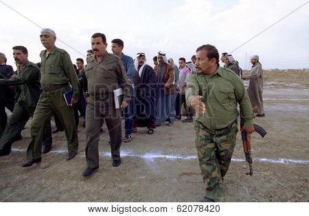 BAGHDAD, IRAQ- MARCH 10: An arms instructor from Iraqi president Saddam Hussein's ruling Ba'ath Party leads Arab and Iraqi men through a military drill on March 10, 1999 in Baghdad, Iraq.