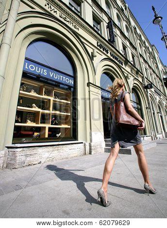 SAINT PETERSBURG, RUSSIA - JUNE 15: An upscale shopper walk by a Louis Vuitton store in Saint Petersburg, Russia on Wednesday, June 15, 2011