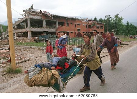 KOSOVO POLJE, KOSOVO, 29 JUNE 1999 --- A Kosovar Gypsy family flees their home after ethnic Albanians sought revenge on Gypsies who collaborated with Serbs during the war of independence.