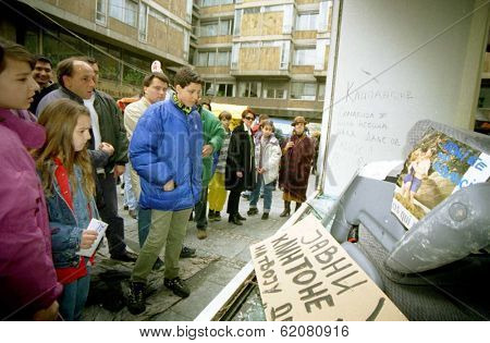 BELGRADE, YUGOSLAVIA - MARCH 30: Belgrade citizens stare through the smashed windows of the American Cultural Center, destroyed by rampaging mobs of angry Serbs protesting NATO airstrikes on March 30, 1999 in Belgrade, Yugoslavia