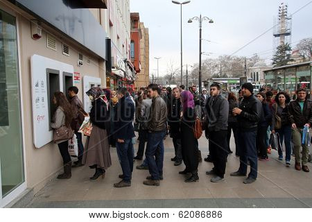 ISTANBUL, TURKEY - SATURDAY, MARCH 8, 2014: Customers wait on line to access money from an ATM machine at a YapiKredit Bank in Istanbul, Turkey, on Saturday, March 8, 2014.