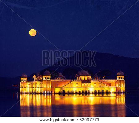 Vintage retro hipster style travel image of Rajasthan landmark - Jal Mahal (Water Palace) on Man Sagar Lake at night in twilight with grunge texture overlaid.  Jaipur, Rajasthan, India