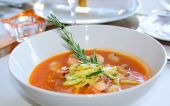 Fish soup with rosemary on restaurant table poster